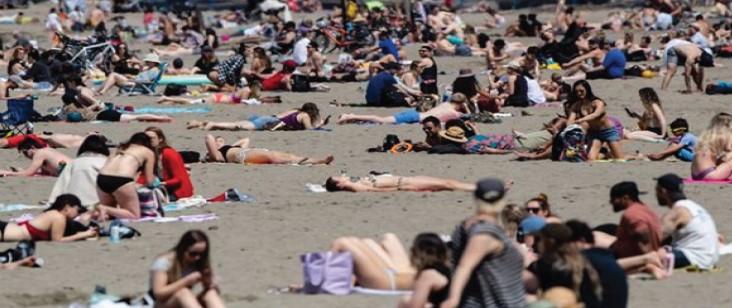코로나 사태가 가라앉는 조짐을 보이고 있는 밴쿠버에서 지난 10일 낮 기온이 영상 20도까지 이르는 따뜻한 날씨에 주민들이 해변가에 몰려나와 일광욕을 즐기고 있다.