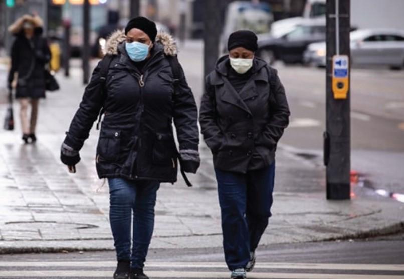 토론토 다운타운에서 마스크를 쓴 주민들이 걸어가고 있다.