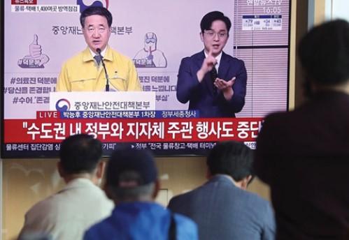 28일 서울역에서 시민들이 박능후 중앙재난안전대책본부 1차장의 코로나19 긴급관계장관회의 결과 브리핑 생중계를 시청하고 있다.