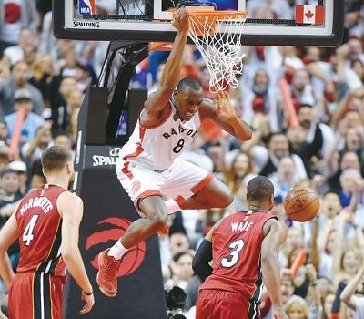 토론토 랩터스의 비스맥 비욤보(가운데)가 15일 에어 캐나다 센터에서 벌어진 프로농구(NBA) 플레이오프 7차전 3쿼터에서 마이애미 히트 드웨인 웨이드(3번)의 마크 위로 솟구치며 덩크슛을 터뜨리고 있다.
