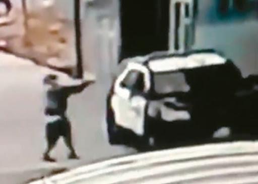 사진설명:한 용의자가 경관 두 명이 앉아 있던 순찰차를 향해 권총을 쏘고 있다. [AP]